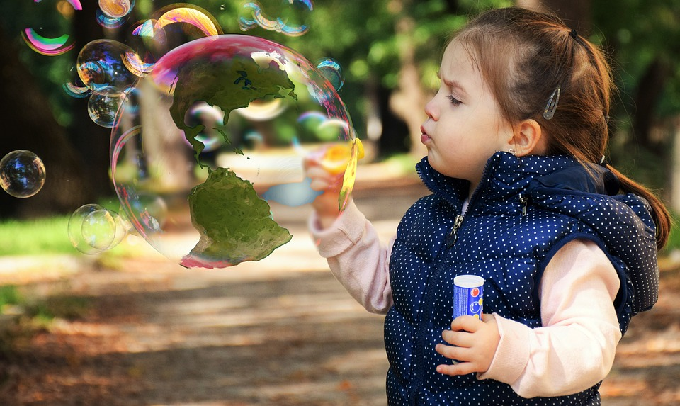 a little child playing blowing balloons