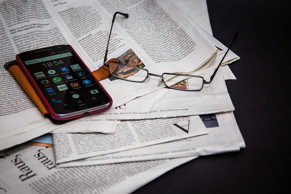 journal, lunettes, téléphone