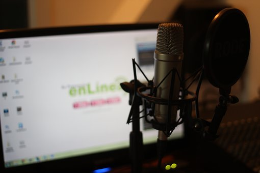 A lit computer screen with a microphone before it to signify podcast