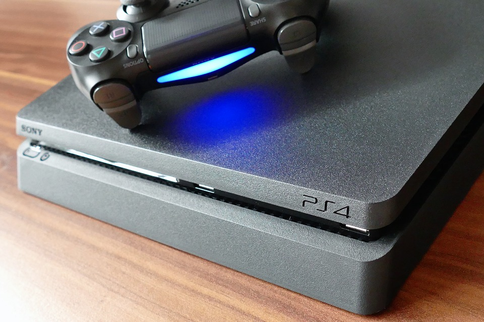 Close-up image of the front of a PS4 with a dualshock controller sitting on top