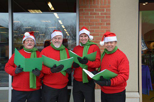 Christmas Carolers, Gentlemen Carolers, four men singing christmas carols all dressed in red jumpers, black trousers and gloves, green scarves and santa hats