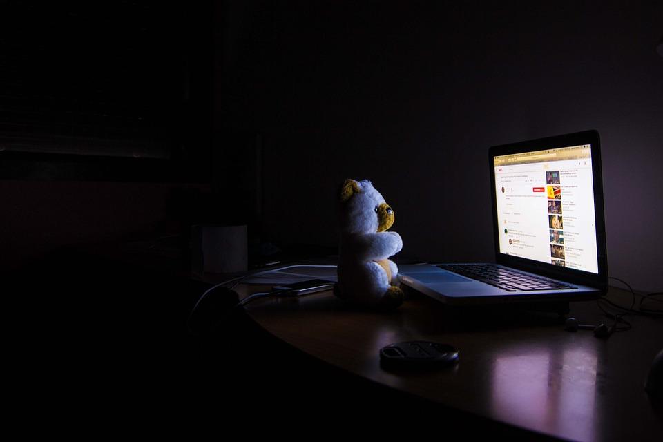 真っ暗な部屋の中で、PCのディスプレイを眺めるクマのぬいぐるみ