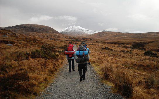 Two people with backpacks hiking through a desert trail