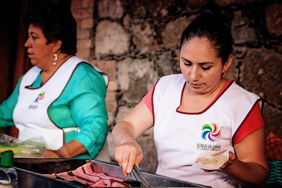 two people cooking street food