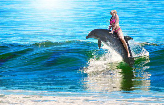 Lady riding a dolphin jumping out of water