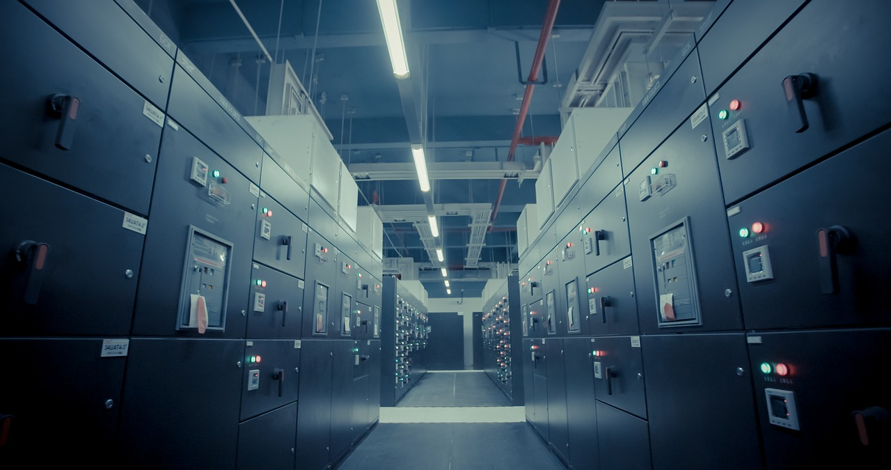 A closed and lit room full of electrical switchgear