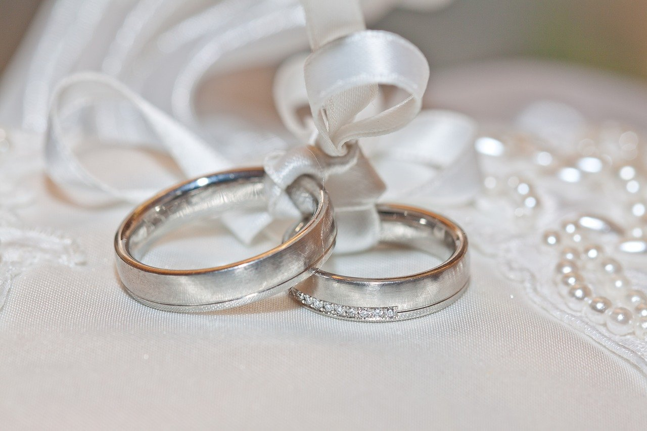Two silver rings tied together by white satin that is embellished with white beads.