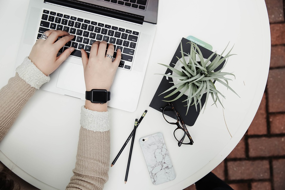 A person is wearing an apple watch while using a laptop and beside it is a pen, eyeglasses, smartphone and a indoor plant