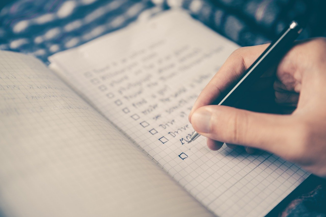 person holding pen checking a checklist