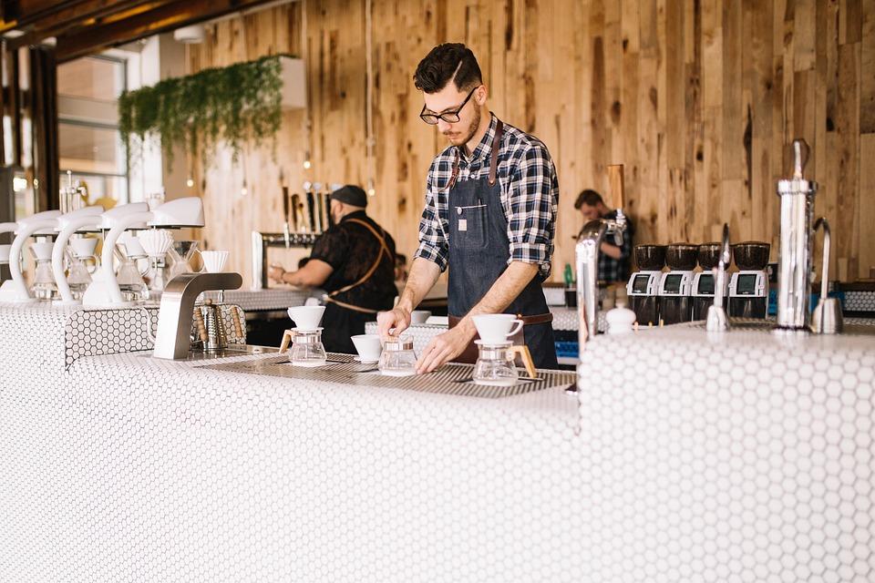 Photo of male barista making coffee