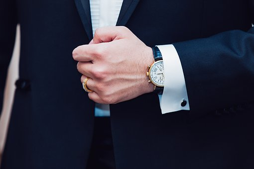 Smart-dressed man in dark suit and expensive watch