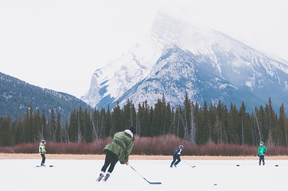 Photograph of people playing ice hockey, with a mountain in the background