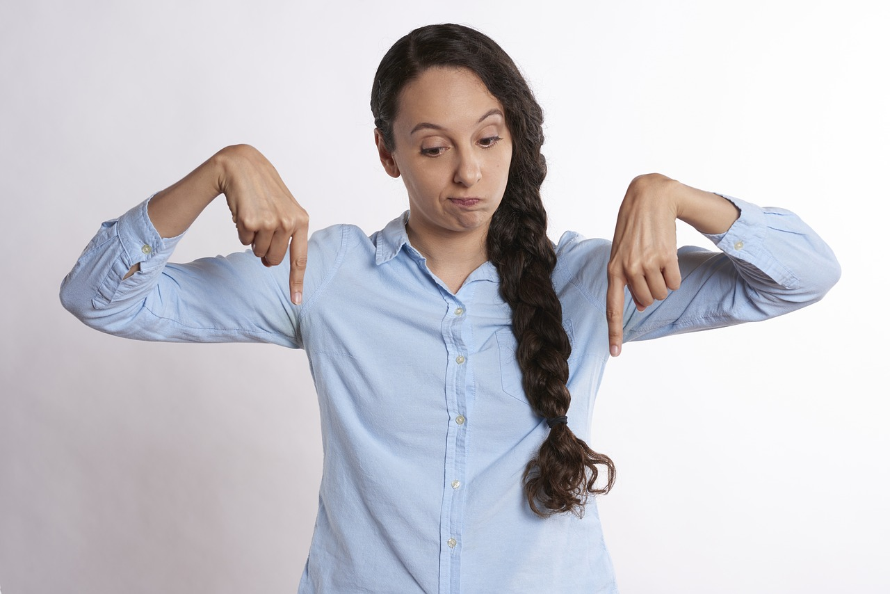 Woman pointing downward with both hands.