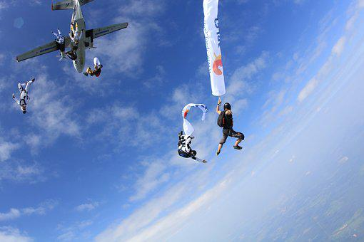 People parachuting out of a plane