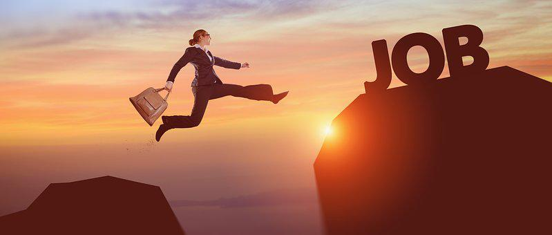 Businesswoman jumping from one mountain toanother in a sunset to signify affiliate challenge
