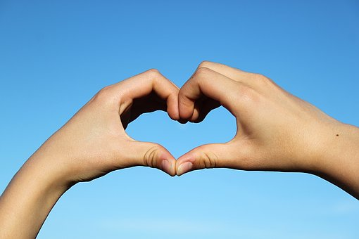 Fingers formed into a heart to signify love