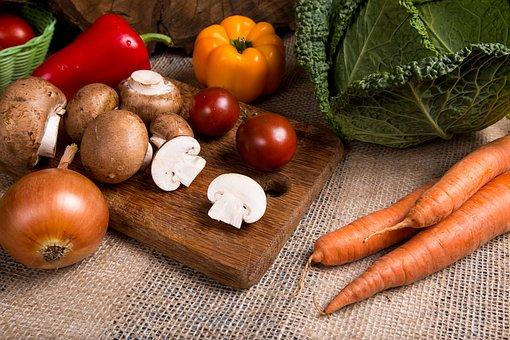 Pieczarki oraz inne warzywa, znajdujące się na drewnianej desce.