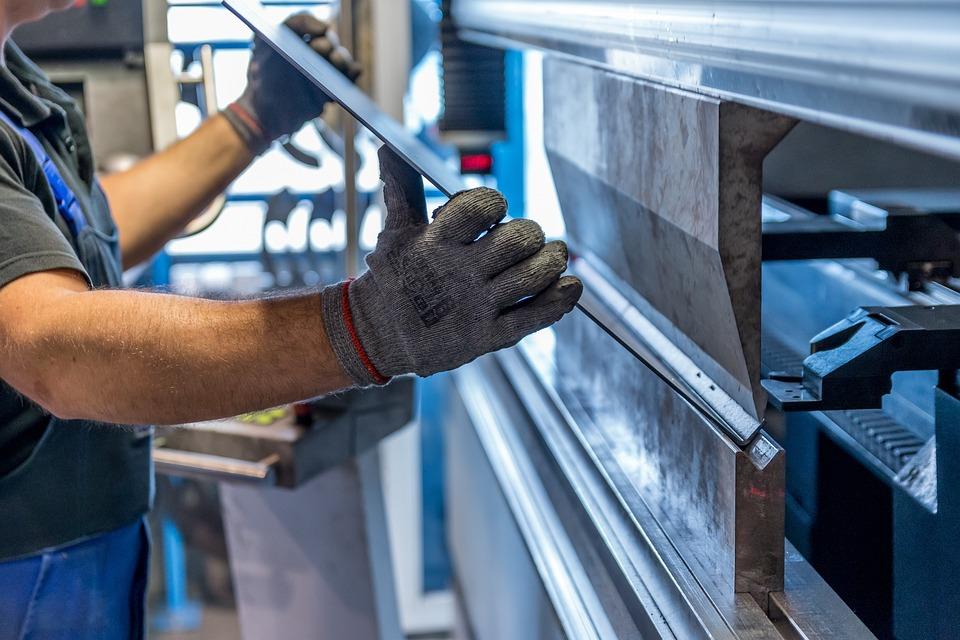 Man holding metal sheet in factory