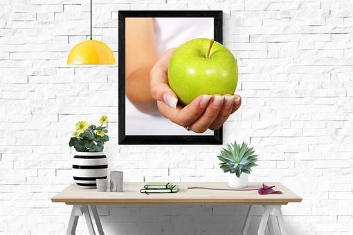 Lady's hand holdingapplethrough a screen on a wall to show affiliate marketing niches and offers