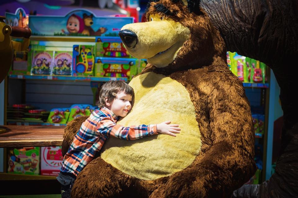 child hugging a big bear