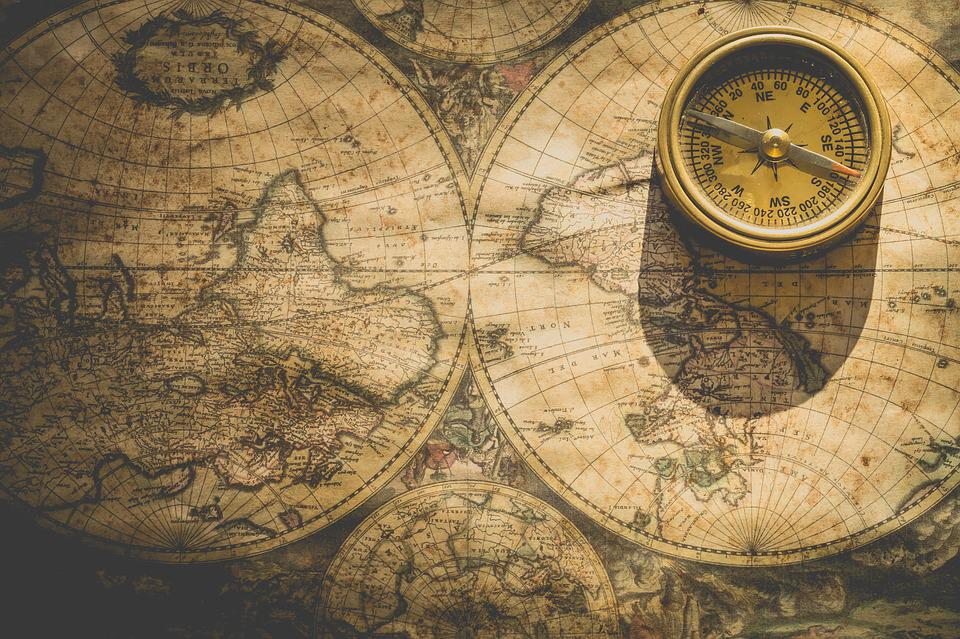 an old fashioned, yellowing map laid out flat and a small yellow compass sitting on top