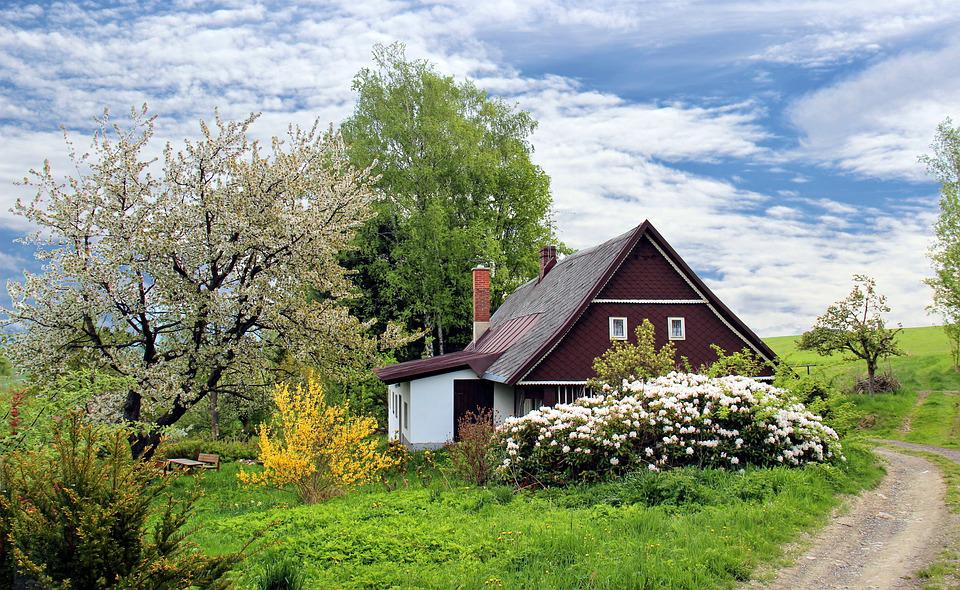 Photograph of a country farmhouse surrounded by colorful trees and shrubs.