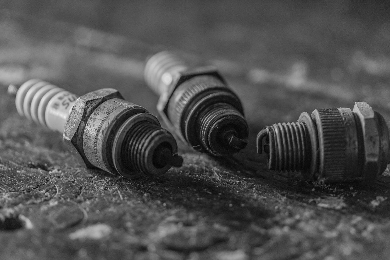 Black and white of three used spark plugs