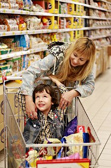 Shopping with the Kids Boy in trolley with Mum looking at products in Supermarket, Shop,