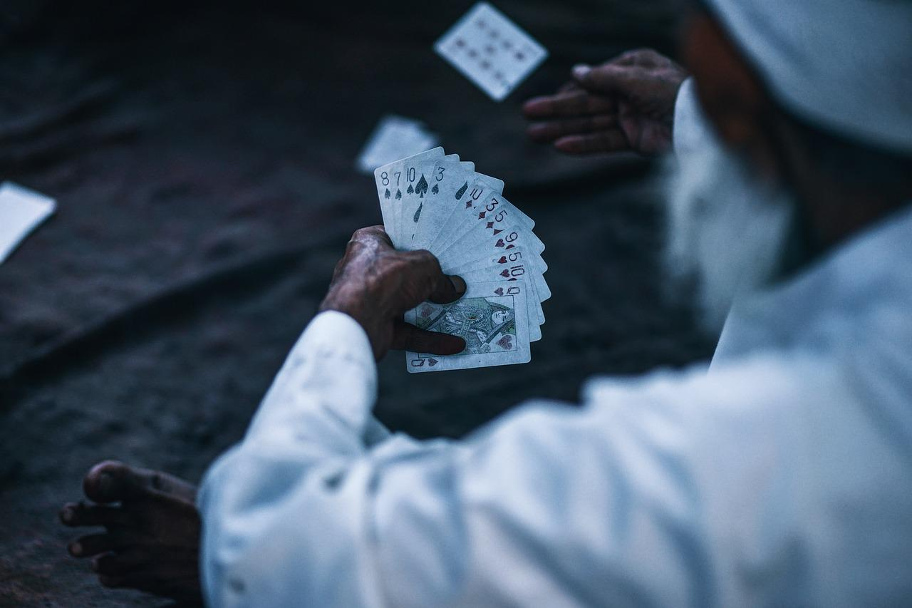 old man holding cards