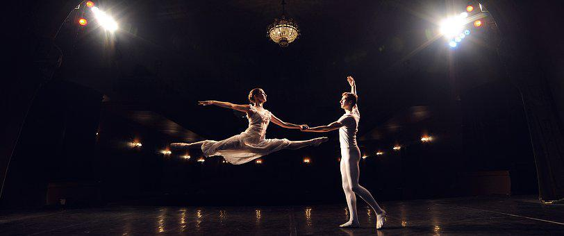 Ballet with woman leaping into air before man with outstretched arms