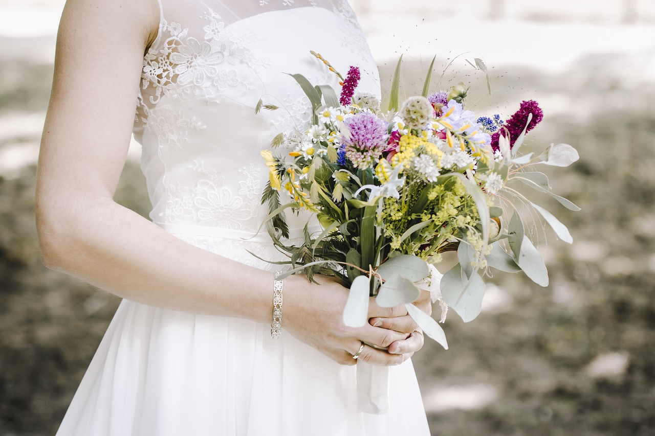 a bride holding a wedding bouquet made up of wildflowers