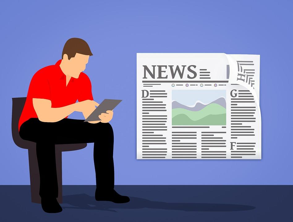 En mann leser nyheter på sitt nettbrett.