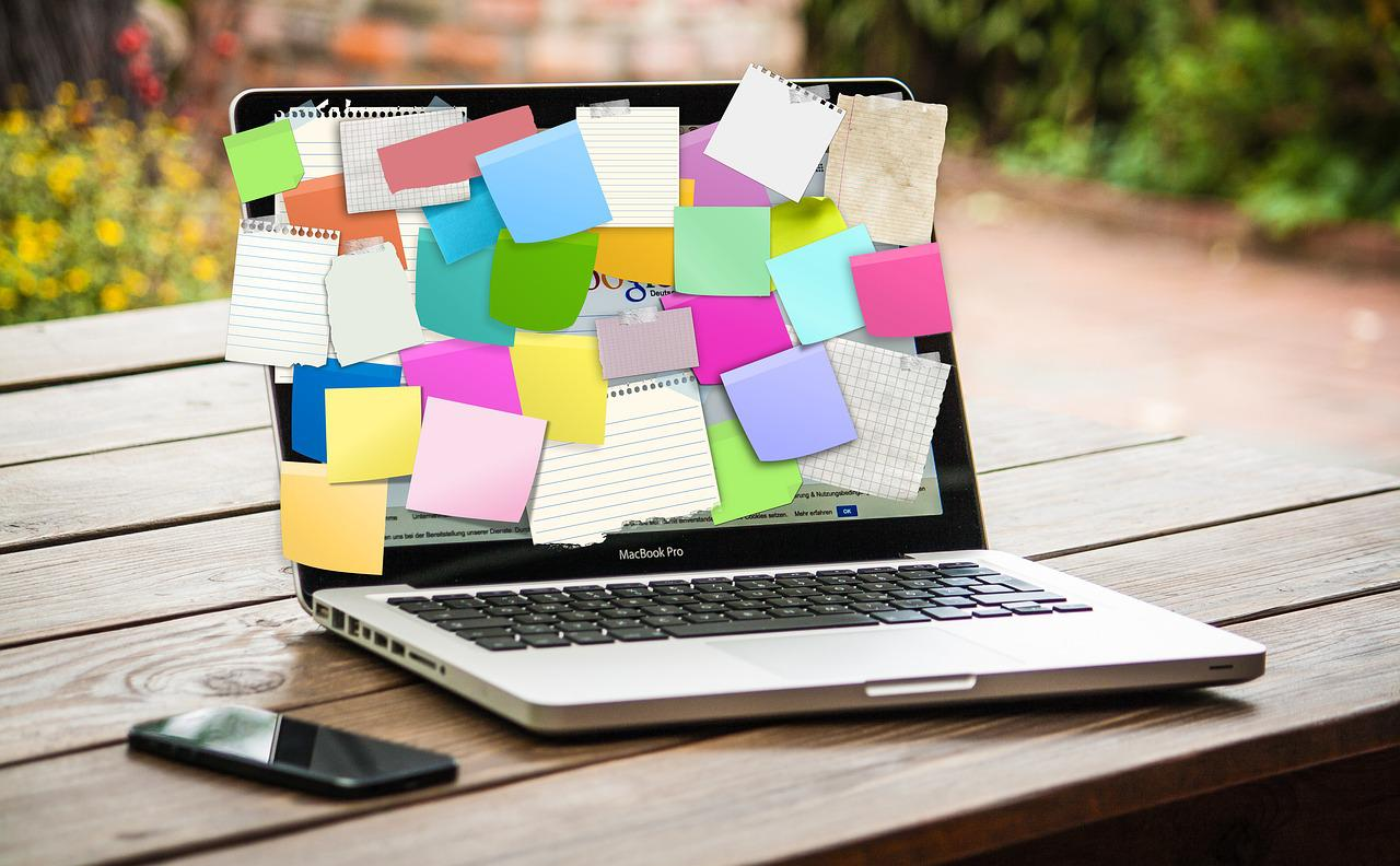 laptop covered in blank sticky notes