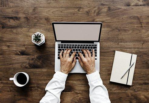 Brazos y manos escribiendo en portatil, con taza de café y libreta con boligrafo