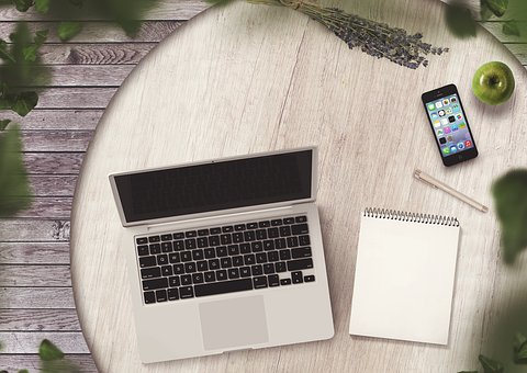 An opened laptop computer on a desk with a telephone, notepad and an apple to signify work from home jobs got easier