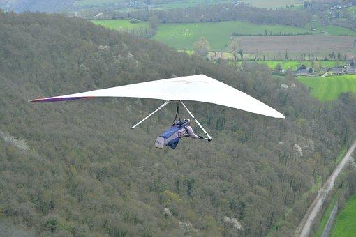 hand glider flying alongisde mountain flank