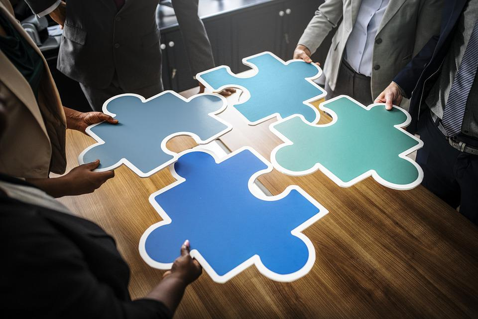 People connecting puzzle pieces together.