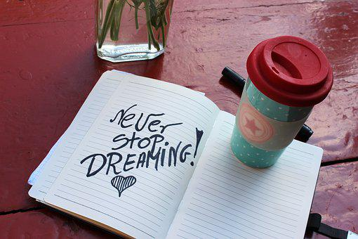 An open book on table with words Never stop dreaming for 301 inspirational and motivational quotes
