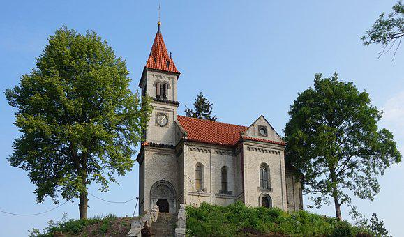 A village church on a hill and 2 trees at the lengths and red tiled roofs