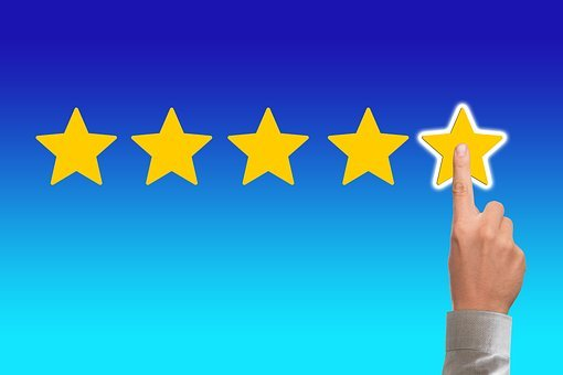 A finger pointing at a fifth yellow star on a bluish background for a feedback