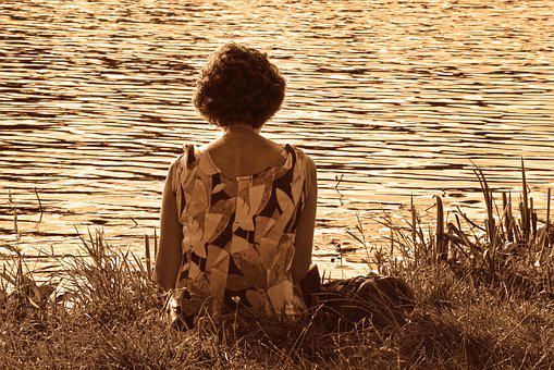 Woman sitting before a tranquil water