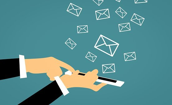 A hand holding a phone from which envelopes are flying to show how doing email marketing