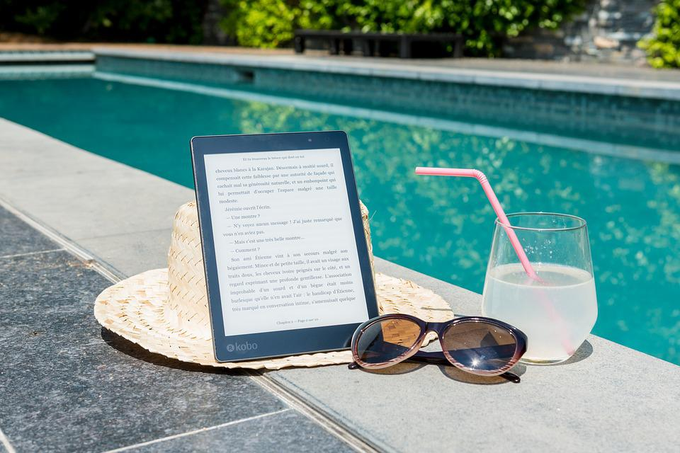 Ipad, sunhat, sunglasses, and drink by pool
