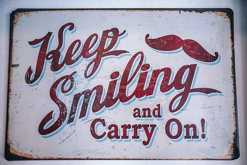 A faded sign carrying the words Keep smiling and carry on! for 301 inspirational and motivational quotes