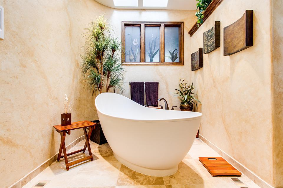 Spa soaking tub with plants and brown towels