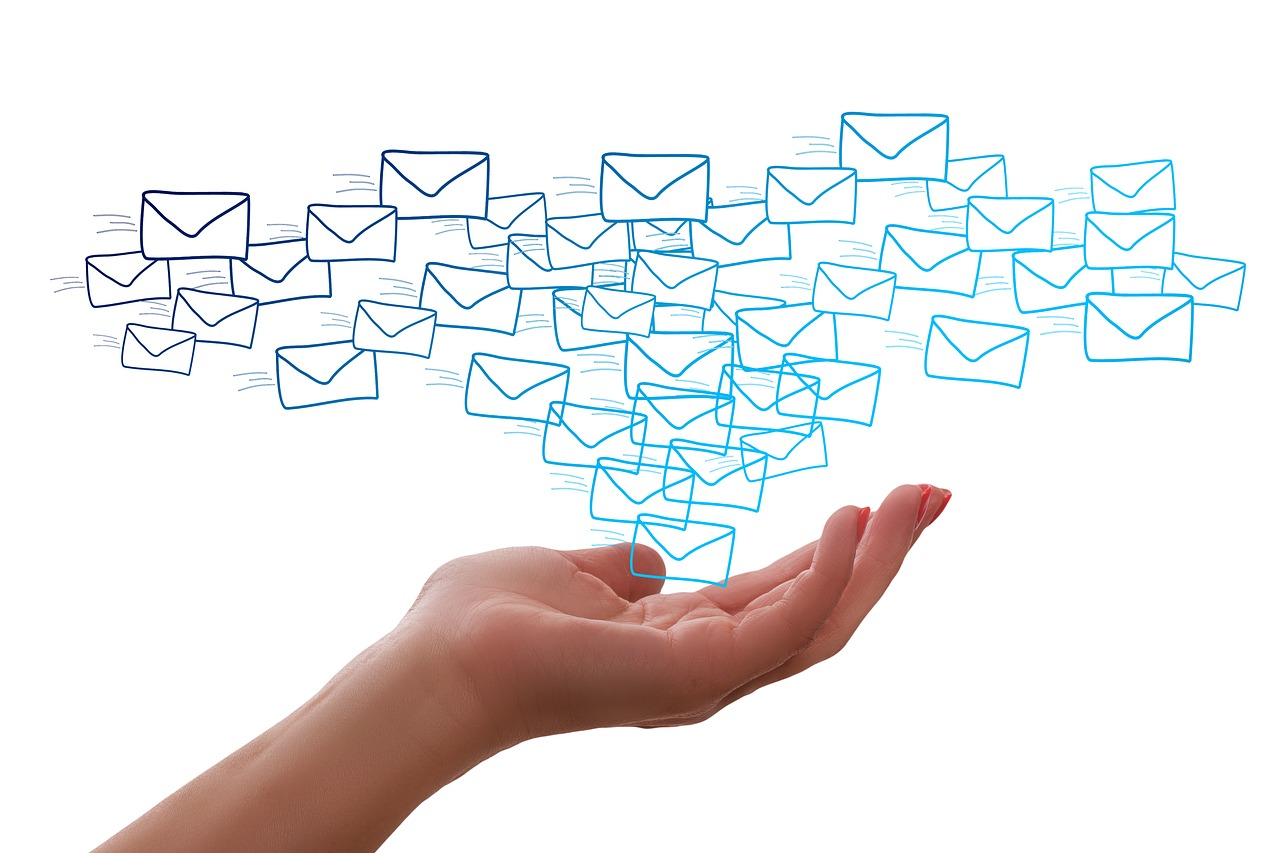 A hand, palm facing up, is  extended towards envelope icons dispersed in the air.