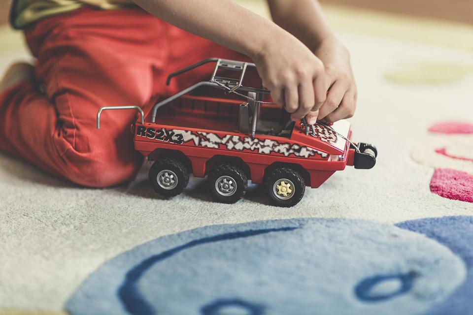 a boy playing car on a rug