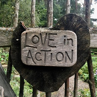 Love in action etched on a wood agaisnt a wooden fence