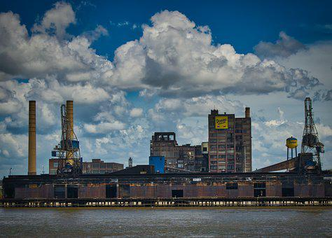 Sugar facrory industry showing chimneys in a cloudy sky before a river