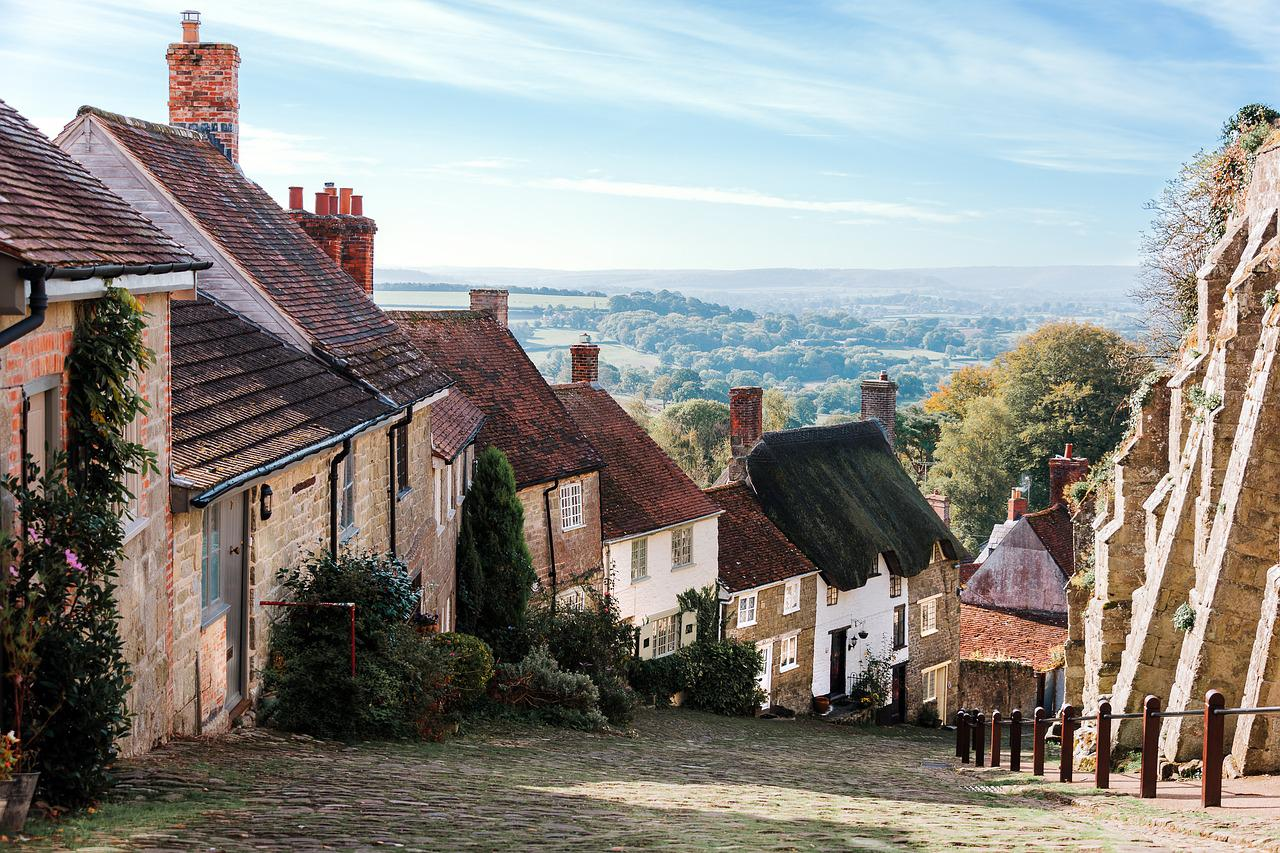 A view of a downward sloping street in England with the village houses made of stone lining the path on the left.